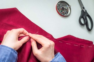 Seamstress sews clothes by hand